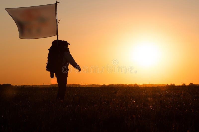 Wandelaar met rugzak en vlag die op het gebied lopen stock fotografie