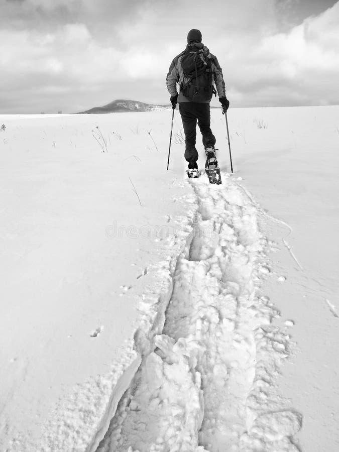 Wandelaar met rugzak het snowshoeing in diepe afwijking Mens met gang in heuvel royalty-vrije stock afbeelding