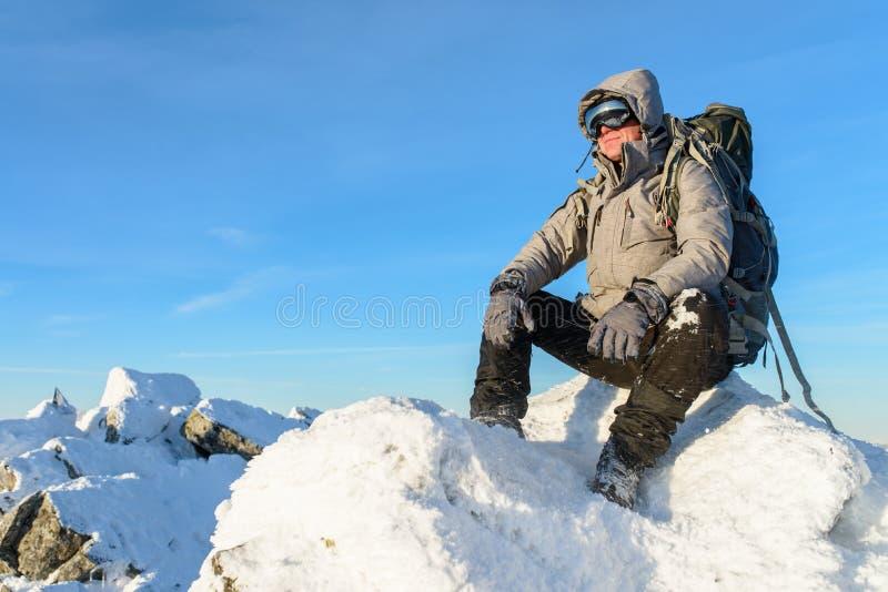 Wandelaar met rugzakzitting en het hebben van rust op de bovenkant van een snow-covered rots over de de winterbergen stock afbeeldingen