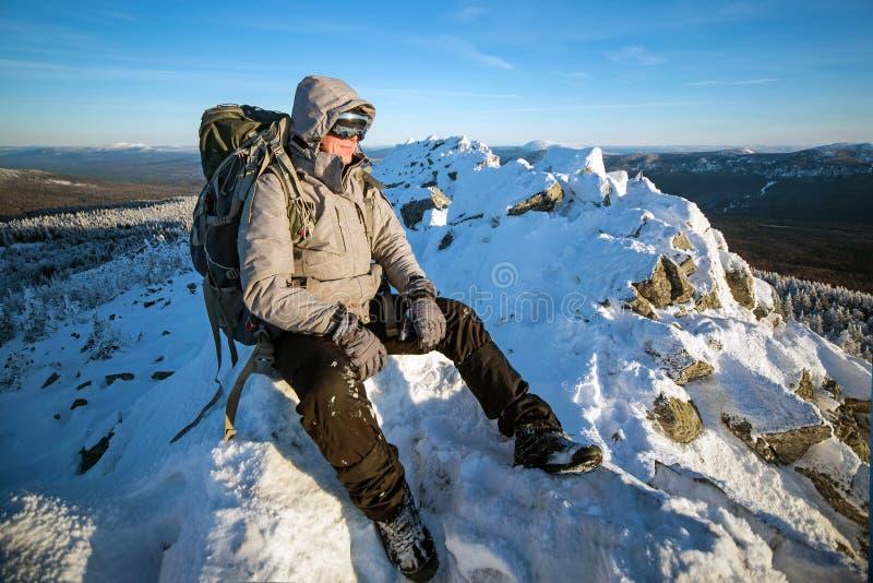 Wandelaar met rugzakzitting en het hebben van rust op de bovenkant van een snow-covered rots over de de winterbergen royalty-vrije stock afbeelding