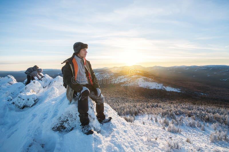 Wandelaar met rugzakzitting en het hebben van rust op de bovenkant van een snow-covered rots over de de winterbergen bij mooi royalty-vrije stock foto