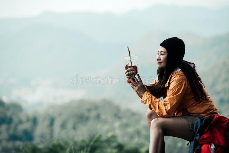 Wandelaar ontspant de Aziatische vrouw zitting en het drinken koffie voor en rust op berg Vrouwelijke avonturenrugzak en reizen d stock afbeelding