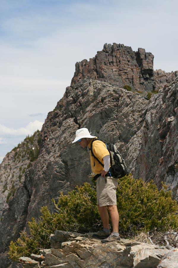 Wandelaar op rand van berg royalty-vrije stock afbeeldingen