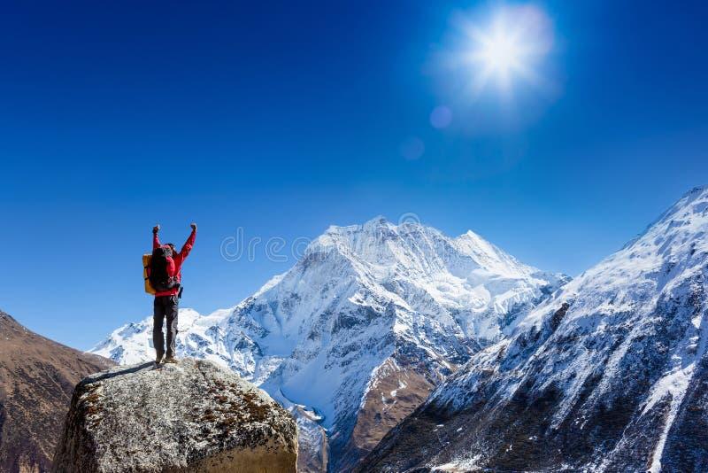 Wandelaar toejuichen verrukt en zalig met wapens hief in de hemel na wandeling op aan berg hoogste top stock fotografie