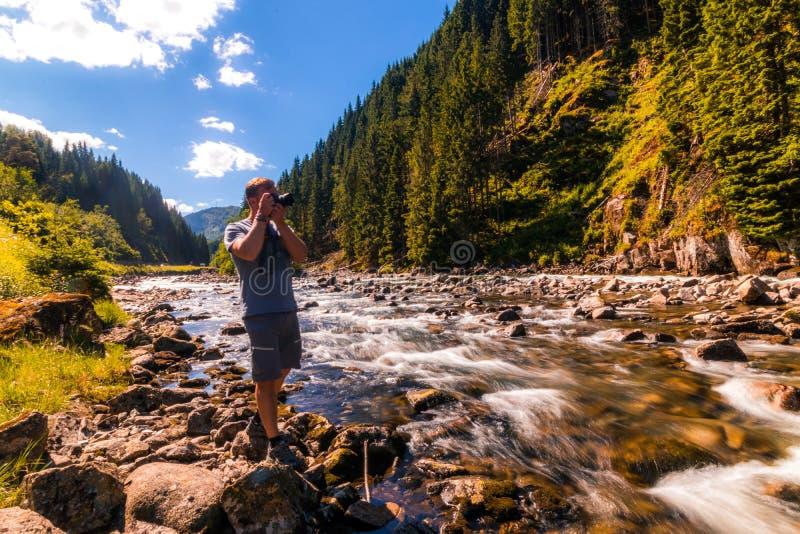 Wandelaareinden op de bank van de bergrivier om een beeld te nemen stock fotografie