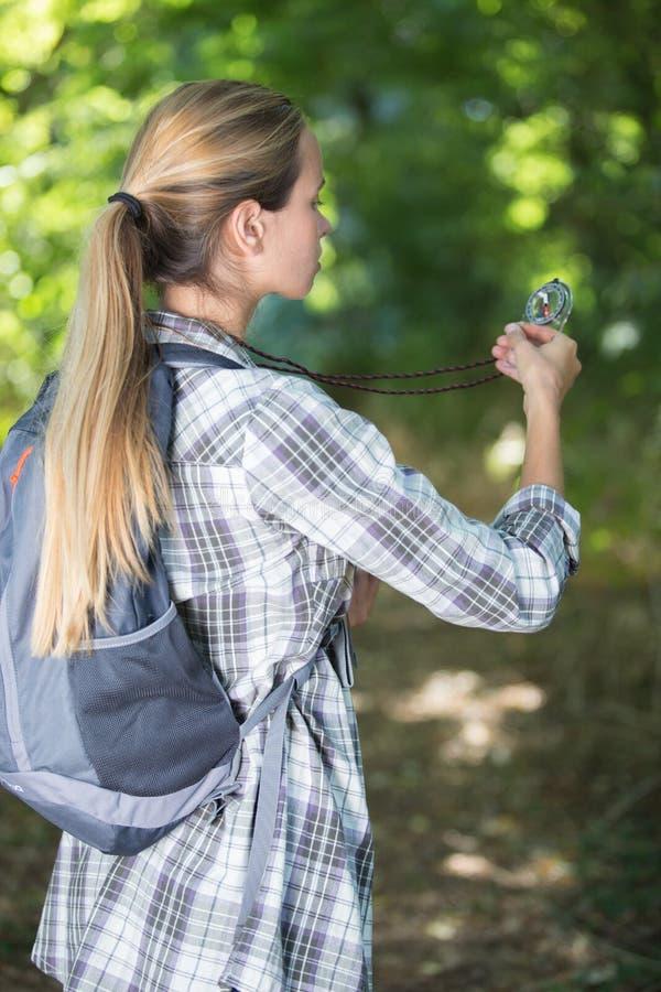 Wandelaarmeisje die richting met kompas zoeken in bos royalty-vrije stock fotografie
