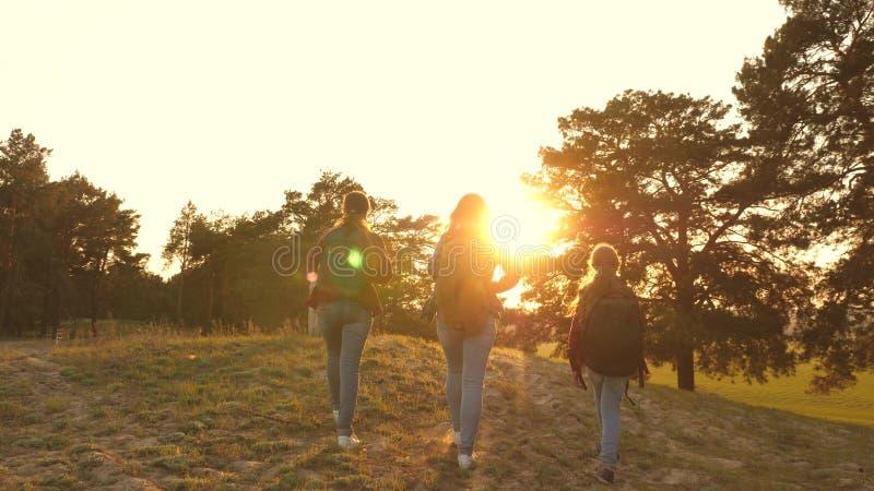 Wandelaarmeisje drie meisjes reizen, lopen door hout om heuvel te beklimmen verheugen zich en opheffen hun handen tot de bovenkan royalty-vrije stock afbeeldingen