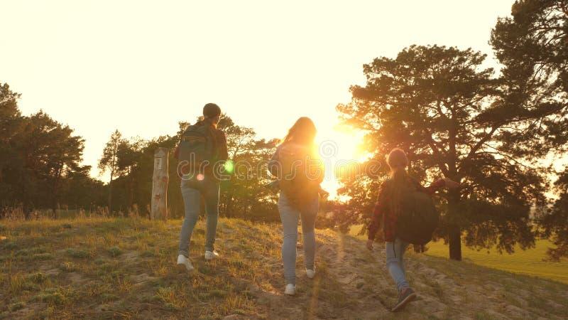 Wandelaarmeisje drie meisjes reizen, lopen door hout om heuvel te beklimmen verheugen zich en opheffen hun handen tot de bovenkan stock afbeeldingen