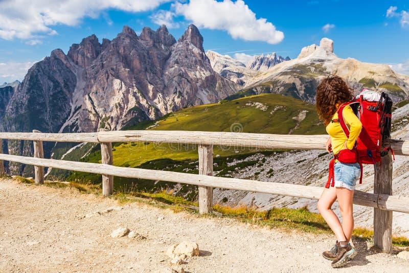 Wandelaarmeisje met rode rugzak die en de mening in Parco Naturale Tre Cime, Dolomietbergen, Italië rusten bewonderen stock fotografie