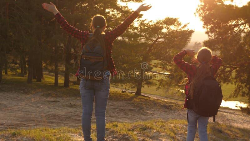Wandelaarmeisje twee meisjes reizen, lopen door bos en golven hun handen op heuvel de meisjes reizen met rugzakken op een land stock afbeeldingen