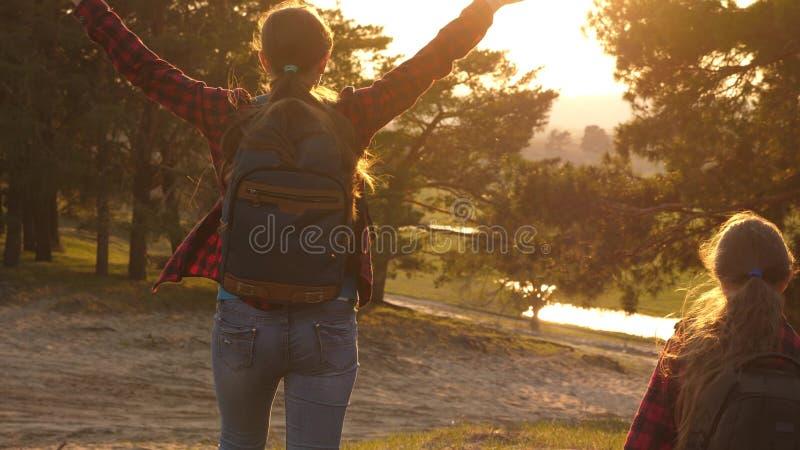 Wandelaarmeisje twee meisjes reizen, lopen door bos en golven hun handen op heuvel de meisjes reizen met rugzakken op een land stock afbeelding