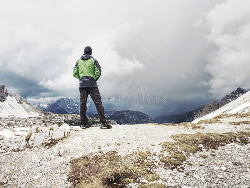 Wandelaarmens die met rugzak stroom op stenen in Dolomiti kruisen royalty-vrije stock afbeelding
