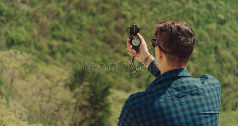 Wandelaarmens die richting met een kompas zoeken openlucht stock afbeeldingen