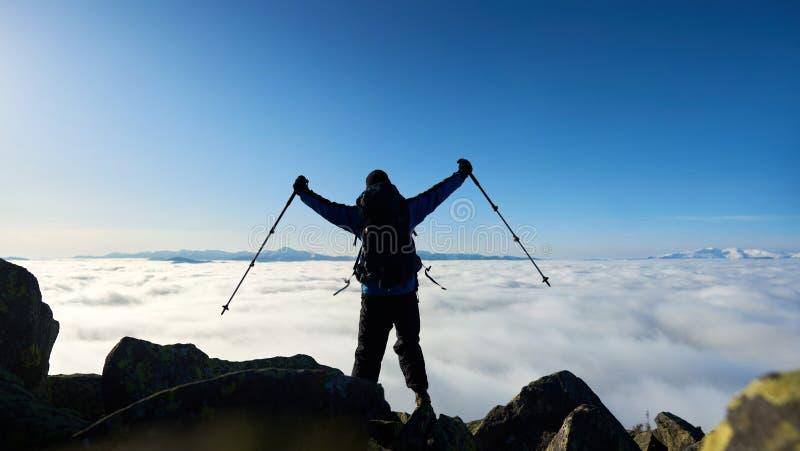 Wandelaarmens op rotsachtige heuvel op mistige vallei met witte wolken, sneeuwbergen en blauwe hemelachtergrond stock foto's