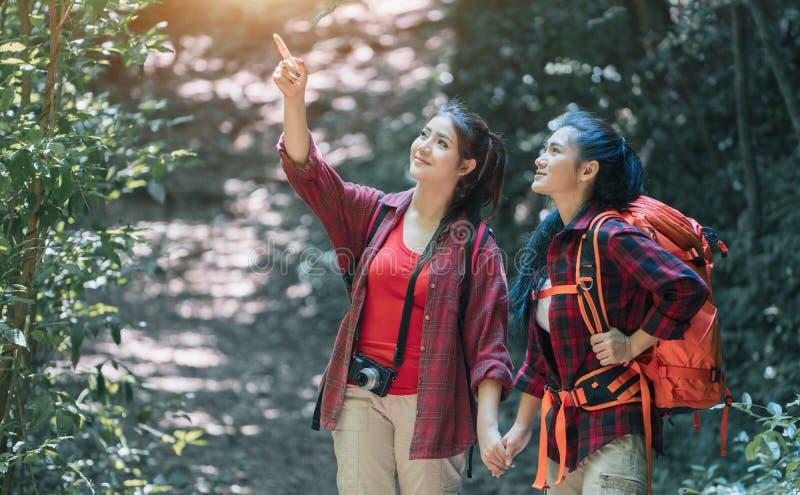 Wandelaars die met rugzakken door een weide met weelderig gras lopen Jong Aziatisch wijfje twee die hipster op bergvakantie wande royalty-vrije stock foto's