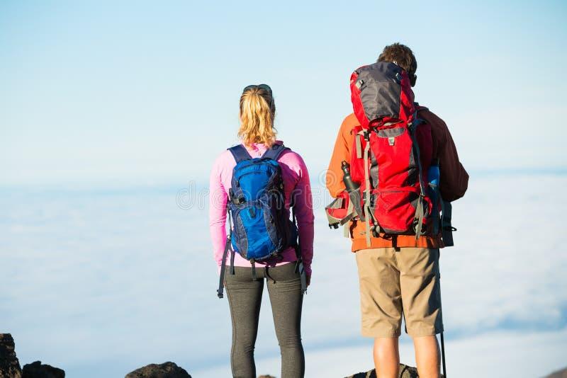 Wandelaars die van de mening vanaf de bergbovenkant genieten royalty-vrije stock foto's