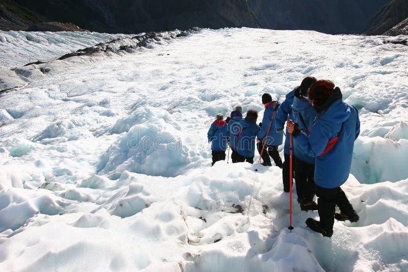 Wandelaars in enig dossier die ruwe ijzige helling dalen bij gletsjerexploratie stock foto's