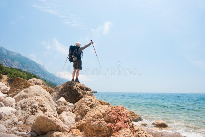 Wandelaars op een steenachtige overzeese kust royalty-vrije stock foto