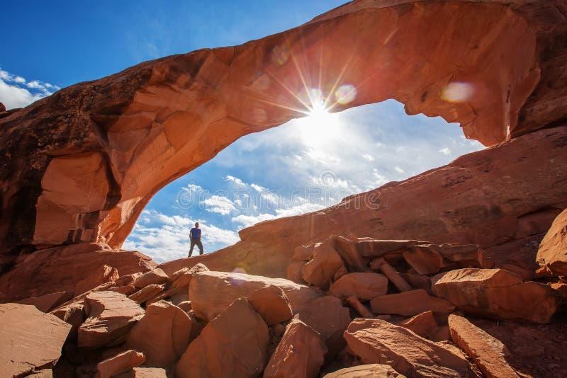 Wandelaarverblijf onder Horizonboog in Bogen Nationaal Park in Utah, de V.S. stock afbeeldingen