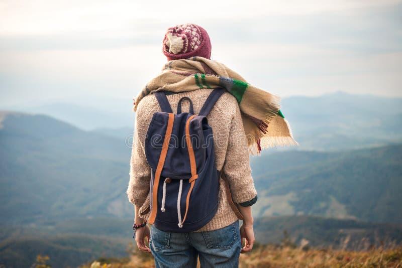 Wandelaarvrouw die in warme kleding met rugzak dragen die in de bergen wandelen stock fotografie