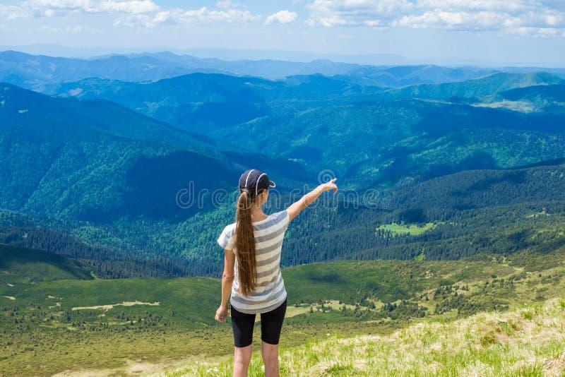 Wandelend meisje bij de piek van de bergpunten aan iets stock foto