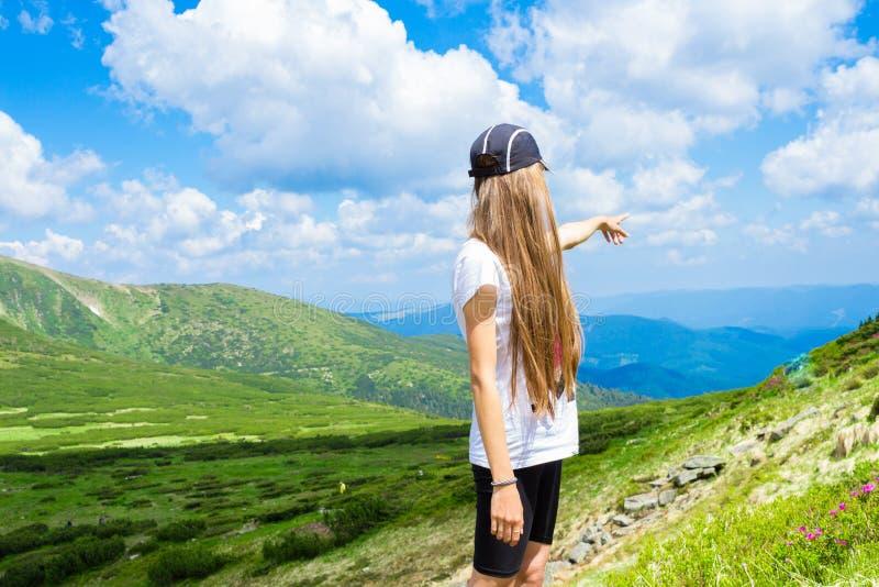 Wandelend meisje bij piek van bergpunten aan iets royalty-vrije stock foto's
