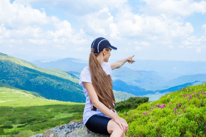 Wandelend meisje bij piek van bergpunten aan iets royalty-vrije stock fotografie