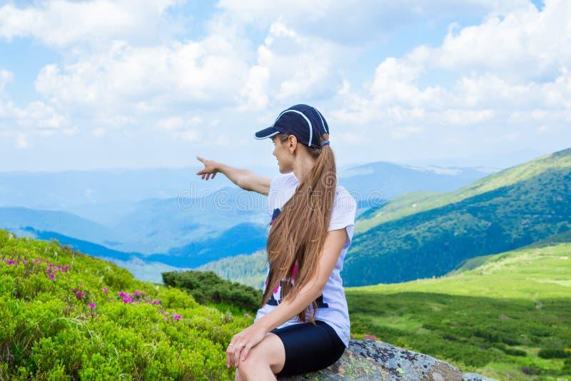 Wandelend meisje bij piek van bergpunten aan iets stock afbeeldingen