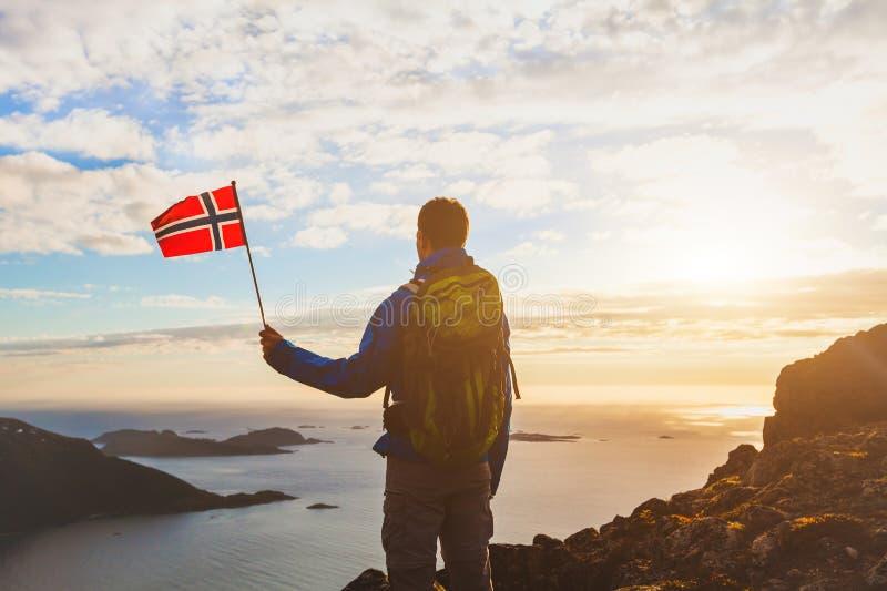 Wandelend in Noorwegen, silhouet van toerist met Noorse vlag royalty-vrije stock foto's