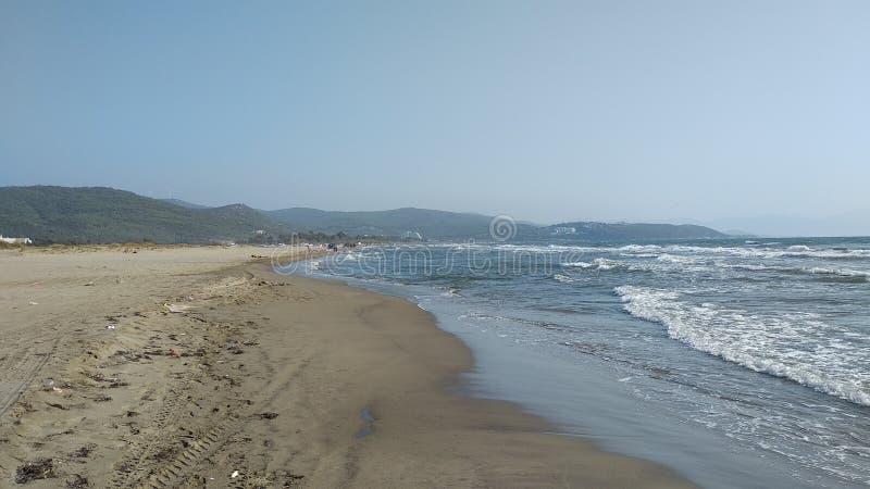 Wandelend op het strand tussen de golven royalty-vrije stock afbeeldingen