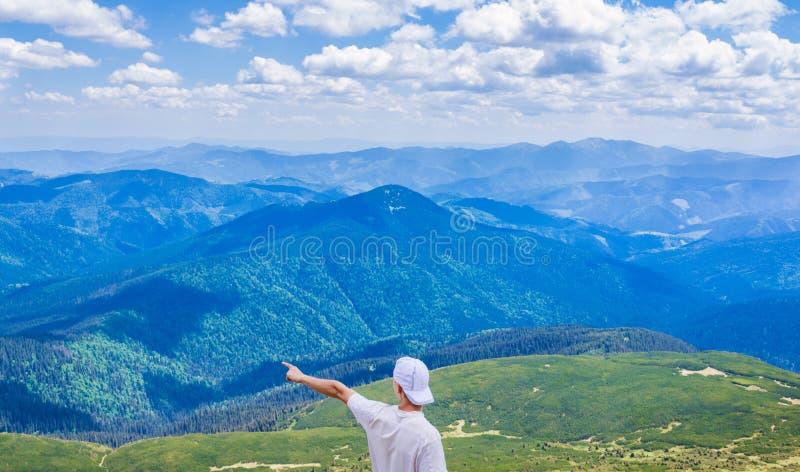 Wandelende mens die op iets met zijn hand richten Hipster het reizen De mens toont richting met zijn binnen hand bovenop klip stock afbeeldingen