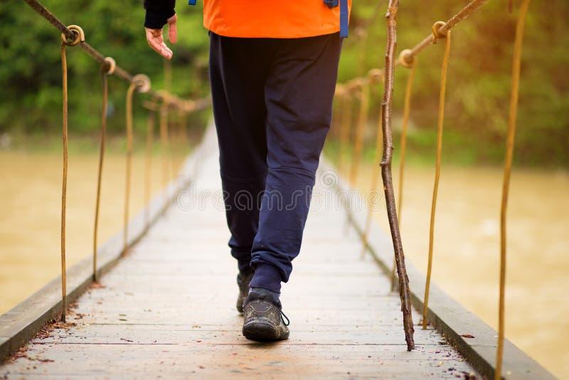 Wandelende mens die rivier in het lopen in saldo op scharnierende brug in aardlandschap kruisen Close-up van mannelijke wandelaar stock foto