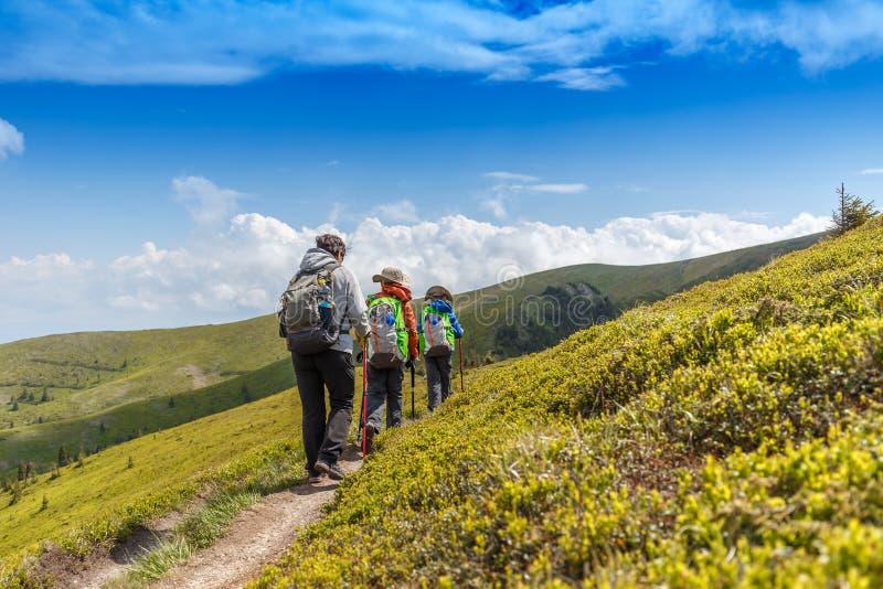 Wandelende vrouw met haar kinderen in Roemeense bergen stock fotografie