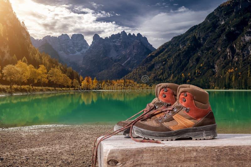 Wandelingslaarzen op houten bank bij Landro-meer in de Dolomietbergen in Italië Italiaans landschap of landschap royalty-vrije stock fotografie