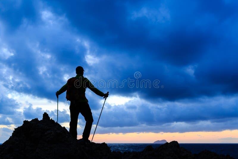 Wandelingssilhouet die backpacker zonsondergangoceaan bekijken royalty-vrije stock foto's