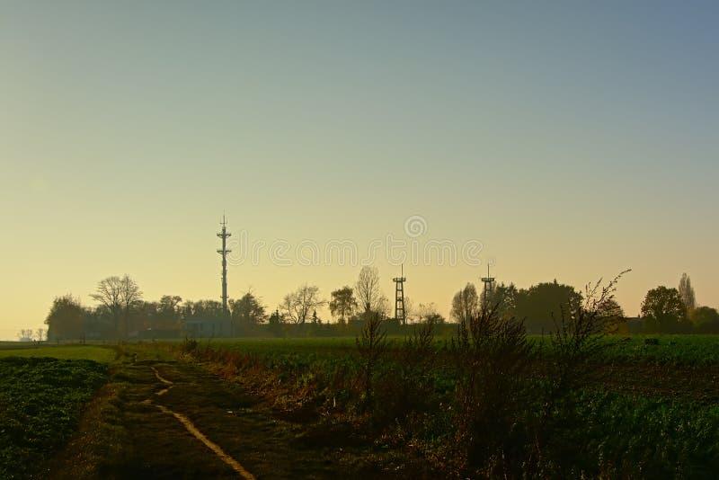 Wandelingssleep door landbouwbedrijflandschap met silhouet van radiotoren en watchtowers van een luchthaven in avondlicht stock afbeeldingen