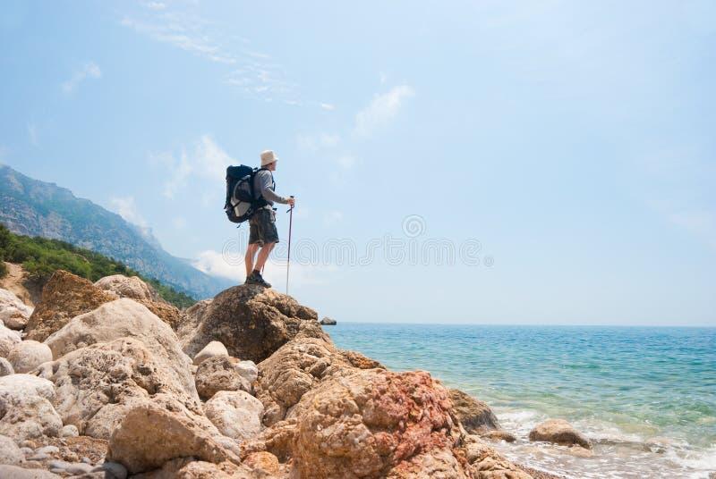 Wanderer auf einem steinigen Seeufer lizenzfreie stockbilder