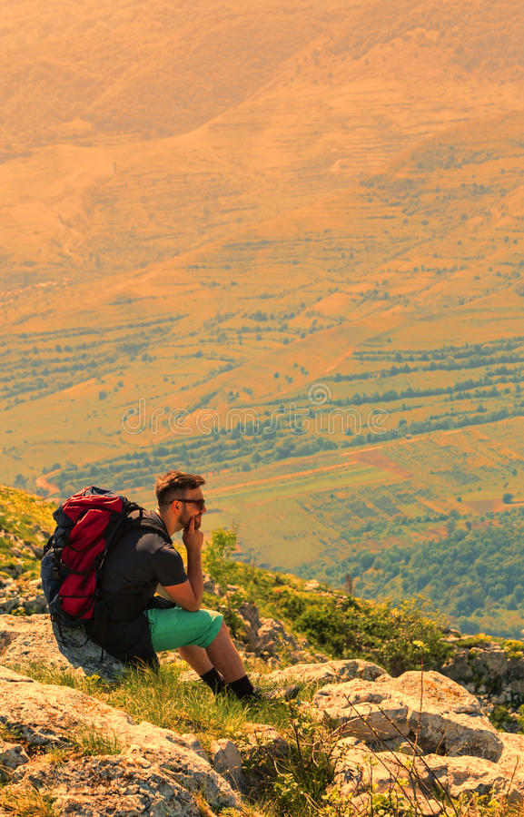 Wanderer, der auf Felsen in den Bergen stillsteht stockbilder