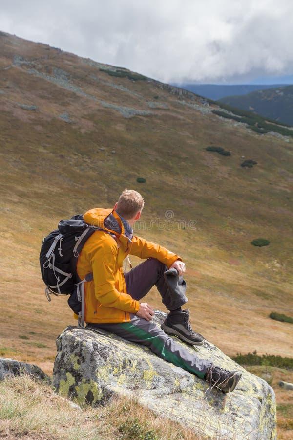 Wanderer, der auf Felsenerbauer in den Bergen sitzt stockbilder