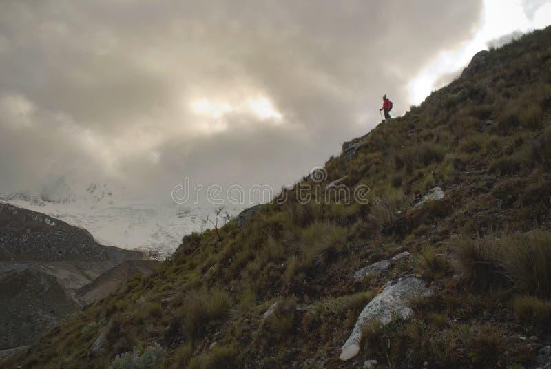 Wanderer, der den Gletscher im Glazial- Tal in der trostlosen peruanischen Berglandschaft anstarrt lizenzfreie stockbilder