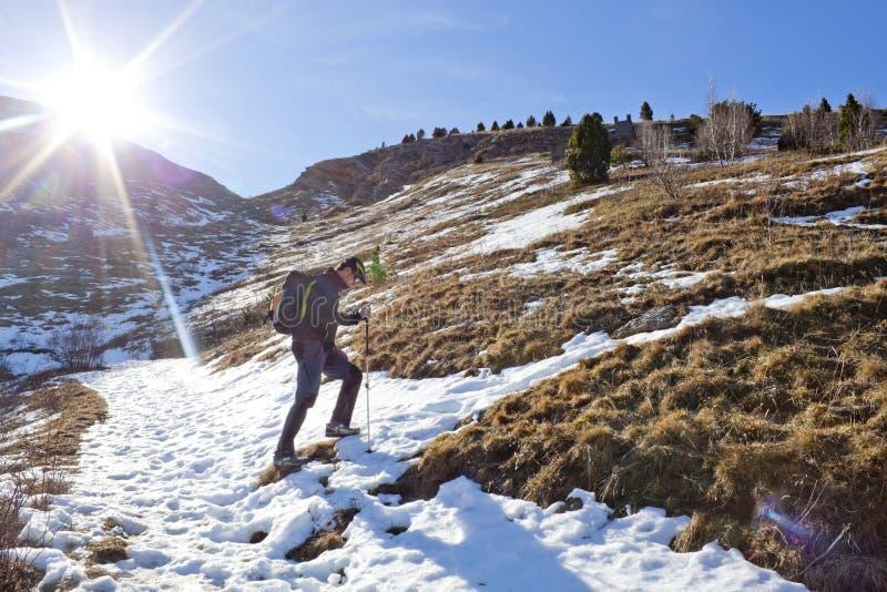 Wanderer, der in den schneebedeckten Berg steigt stockbild