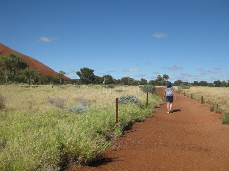 Wanderer, der die 10km Bahn, niedrige Wegspur Uluru geht stockbild