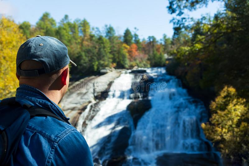 Wanderer, der die Schönheit von hohen Fällen in Du Pont Zustands-Wald im Fall genießt lizenzfreie stockbilder
