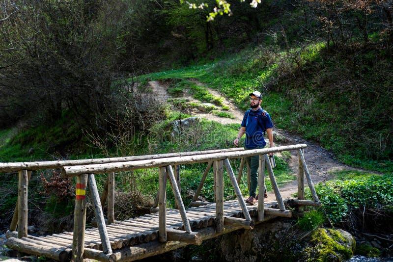 Wanderer, der draußen die Holzbrücke kreuzt stockfoto