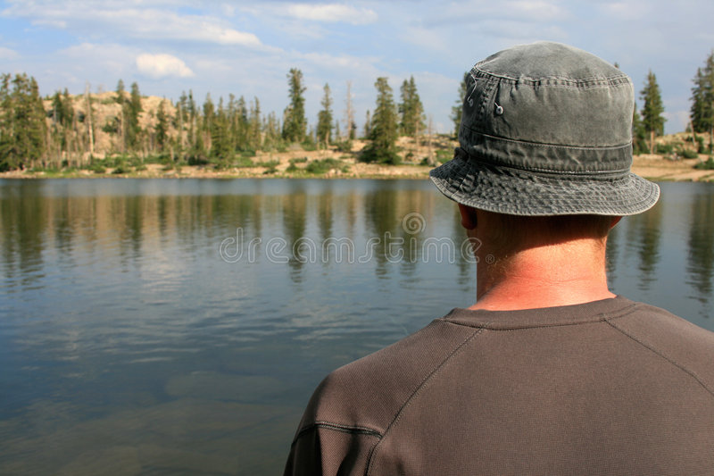 Wanderer, der heraus über See schaut stockfotografie