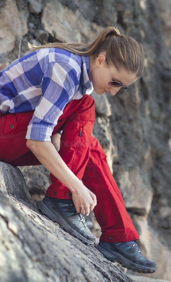 Wanderer, der ihre Schnürsenkel repariert lizenzfreie stockfotos