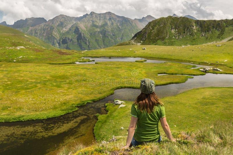 Wanderer der jungen Frau genießen die Ansicht über Bergspitzeklippe und -fluß am sonnigen Tag stockbilder