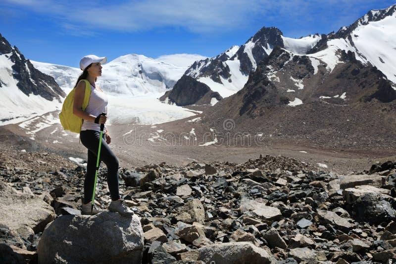 Wanderer der jungen Frau mit Rucksack in den Bergen mit Gletschern lizenzfreies stockbild