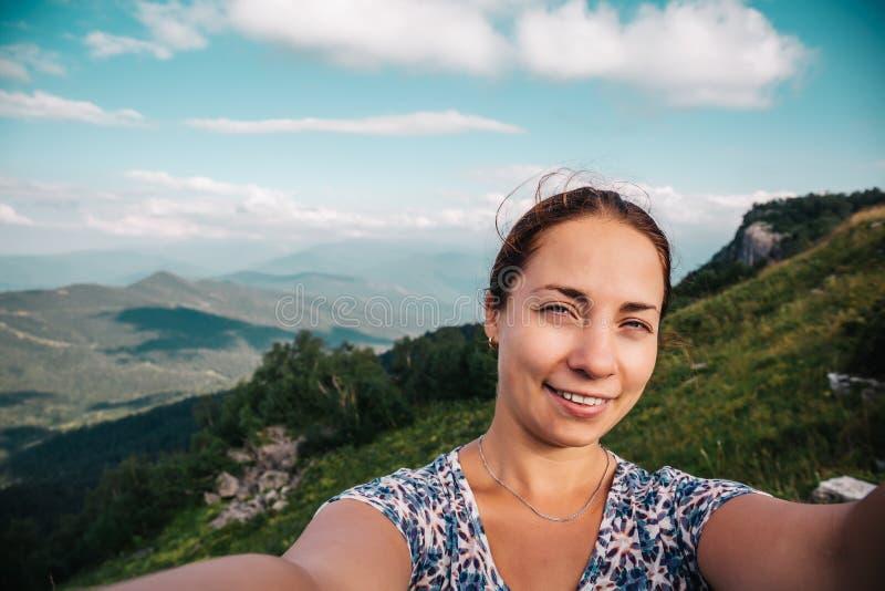 Wanderer der jungen Frau, der selfie oder Foto mit intelligentem Telefon an der Bergspitze mit Berglandschaftshintergrund lächelt stockfotos