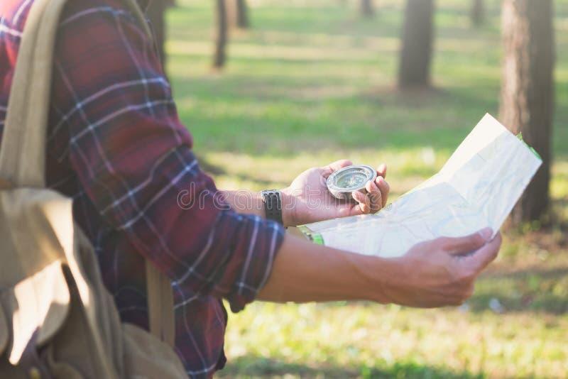 Wanderer, der Richtung mit einem Kompass im Wald sucht lizenzfreies stockfoto